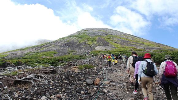 肩の小屋から山頂を目指す登山者