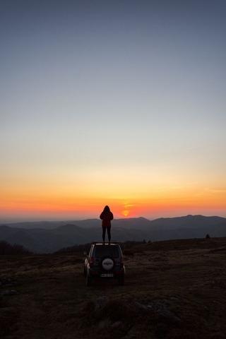 ジープで日の出を見る人