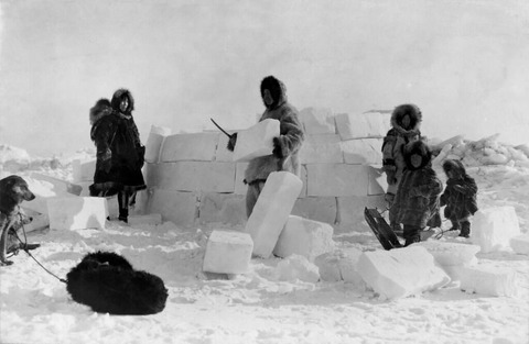 Group of Inuit people building an igloo