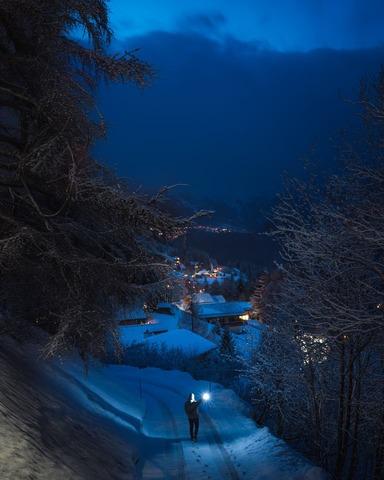 暗い中ライトを点けて歩く人