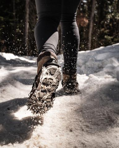 軽アイゼンで雪上を歩く女性