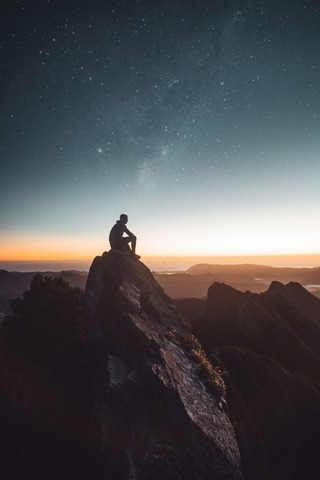 山頂から夕暮れを見る登山者