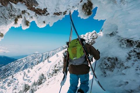 スキー板を担いで雪山を登る人