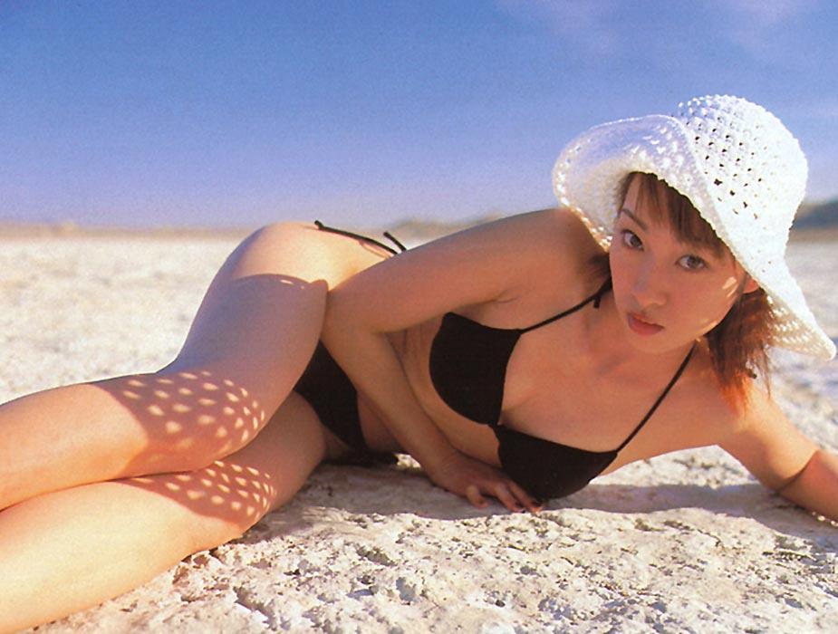 黒い水着で砂浜に横たわりこちらを見つめる坂下千里子