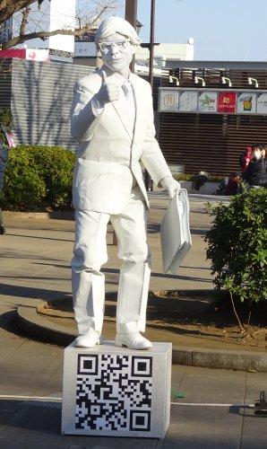 全身を真っ白に塗った大道芸人のパントマイム「人間彫刻 白リーマン」