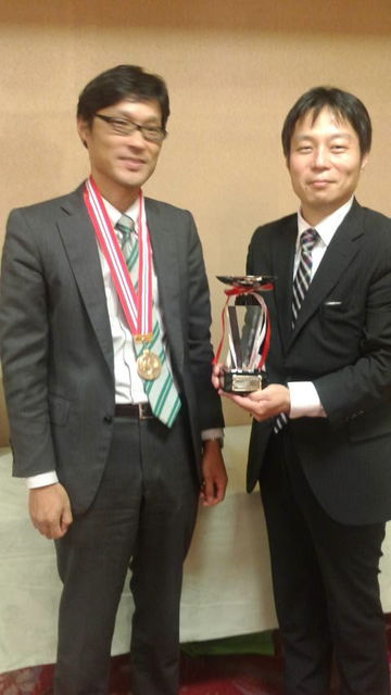 (12)トロフィーとメダルを持つ優勝者2人