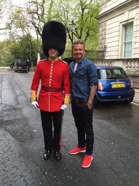 上は紺のデニムシャツ、下は黒デニム、ベルトの茶色と赤のスニーカーがアクセントでカッコいいデビッド・ベッカム。靴の色が隣の近衛兵の服とマッチしていいですね。