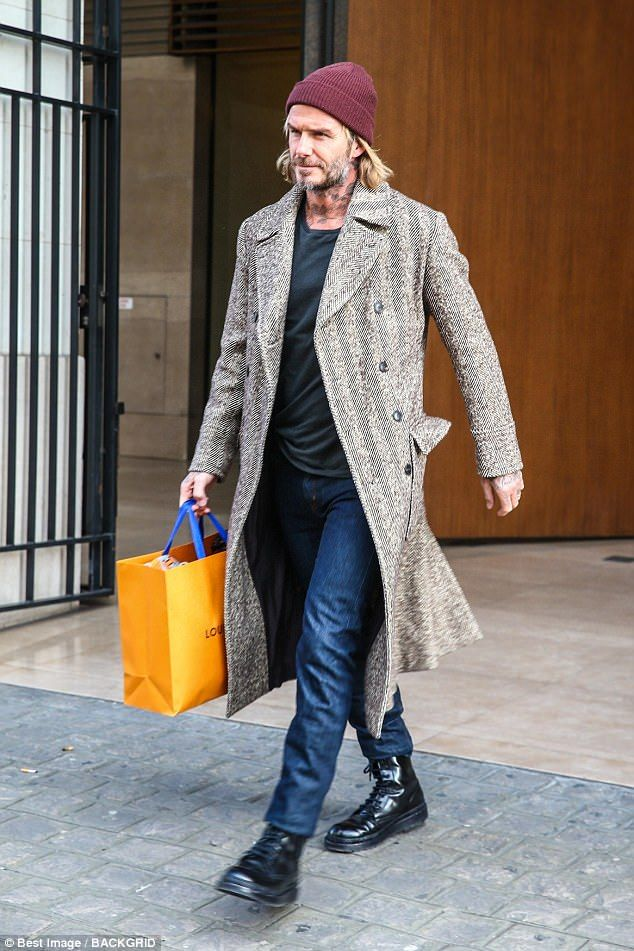 ルイヴィトンの紙袋を手に歩くデビッド・ベッカム ツイードのロングコートに黒のシンプルインナー、デニム、編み上げブーツ、ニット帽のデビッド・ベッカム。