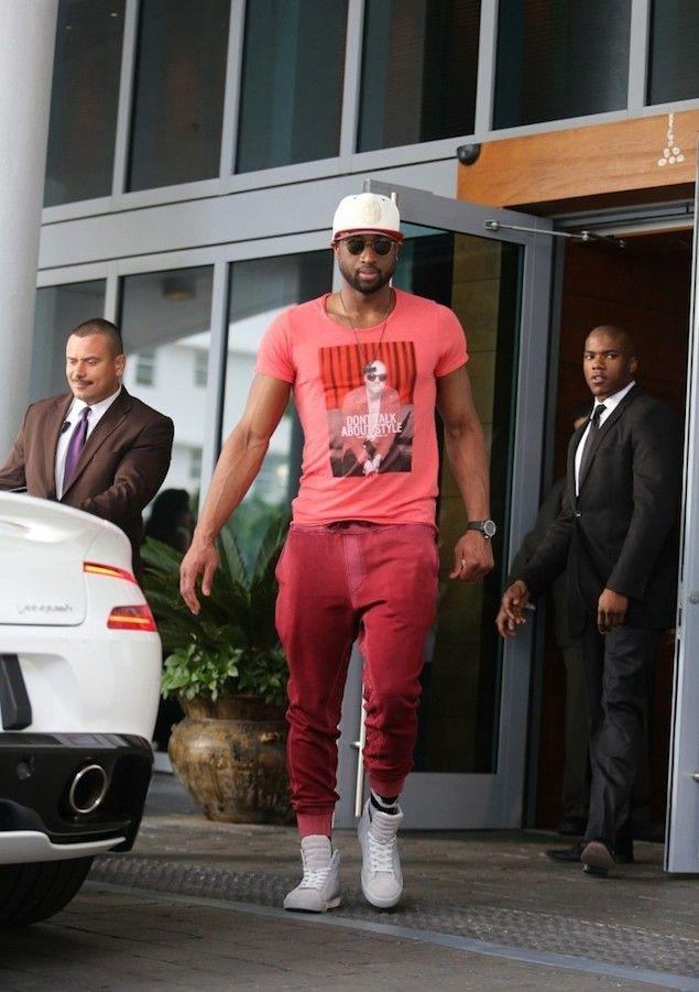 均整の取れた筋肉質の体にピンクのプリントTシャツにを着て同系色のスウェットパンツをあわせるNBAスター、ドウェイン・ウェイド。白のハイカットスニーカーに