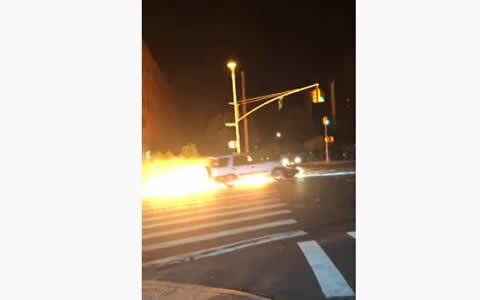 Car Pushes Flaming Motorcycle down Street