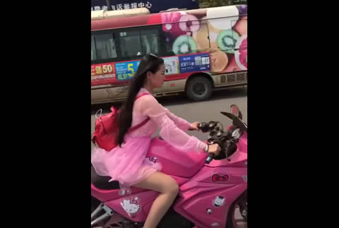 Chinese girl riding her hello kitty pink motorcycle
