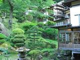 山の斜面に立つ庭園と鯉の泳ぐ池 手入れが良い
