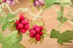 グリーンの実をつけた和紙製の植物を使ったモダンな一輪挿しパネル(赤や紫の実)