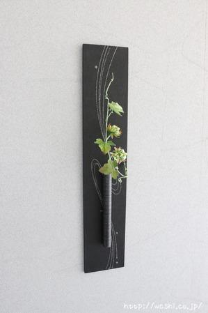 グリーンの実をつけた和紙製の植物を使ったモダンな一輪挿しパネル(斜めから)