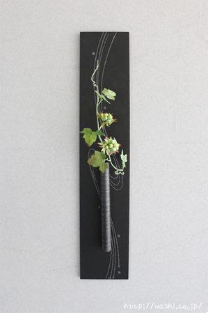 グリーンの実をつけた和紙製の植物を使ったモダンな一輪挿しパネル(正面から)