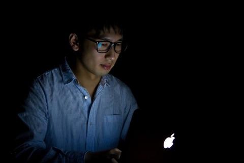 薄暗い部屋でパソコンを眺める男性-580x387
