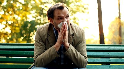 stock-footage-sick-man-blowing-his-nose-into-tissue-outdoors
