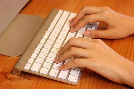 Macのキーボードを打つ女性の指