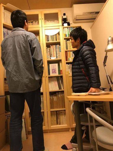 養気院の問診室の本棚の前で