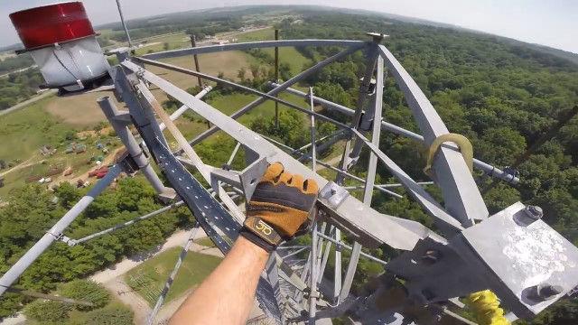 携帯電話の基地局タワーのてっぺんに登り、航空障害灯を修理する高所作業員視点の映像