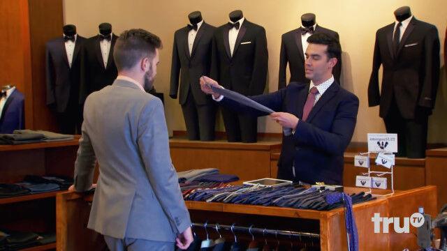 名刺サイズのカードがスーツ上下に展開!?ショップ店員に扮して信じがたい性能のニセ商品を売り込むマジシャン