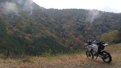 林道を抜けた先にある丘とバイクの風景写真