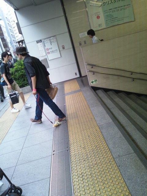 代々木駅でトウモロコシにリードつけて散歩してる