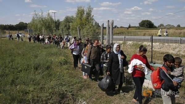 migrants-walk-along-a