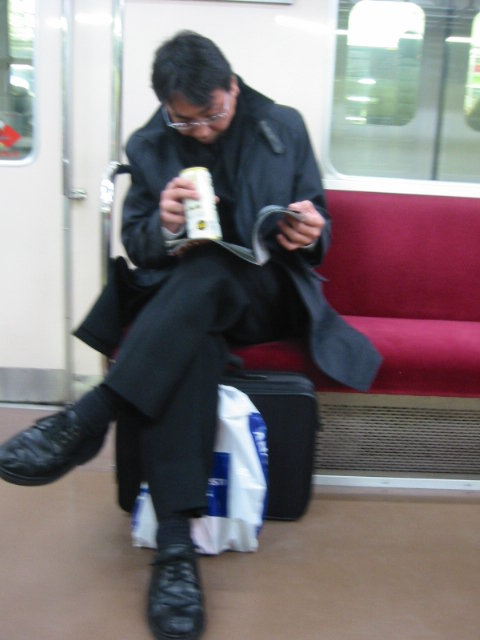 man drinking beer on train